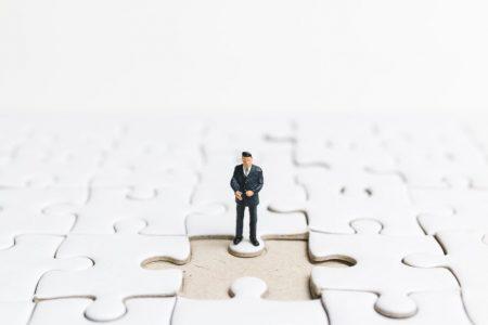 Miniature people: Businessman standing on white jigsaw.